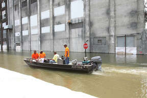 Alton City workers boat down West Broadway Friday to help drop sandbags on the river side of the floodwall.