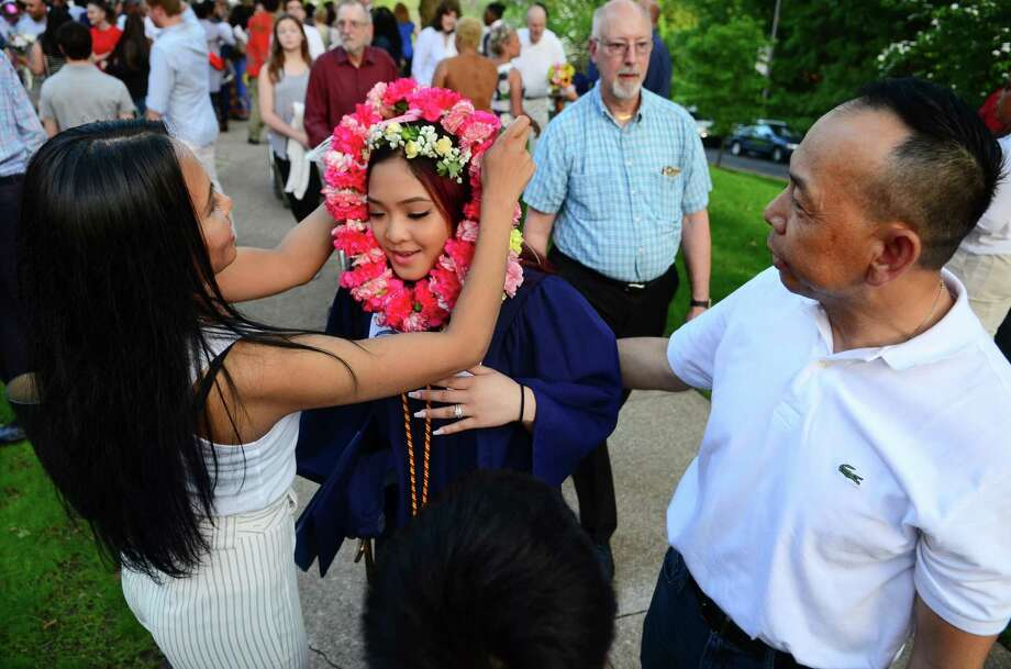 Graduate Lanee Kingrasaphone is presented a lei by her aunt Mia Puttasodd after Notre Dame of Fairfield's Commencement Exercies in Fairfield, Conn., on Friday May 31, 2019. At right is Lanee's stepdad Scott Venethongkham. Photo: Christian Abraham / Hearst Connecticut Media / Connecticut Post