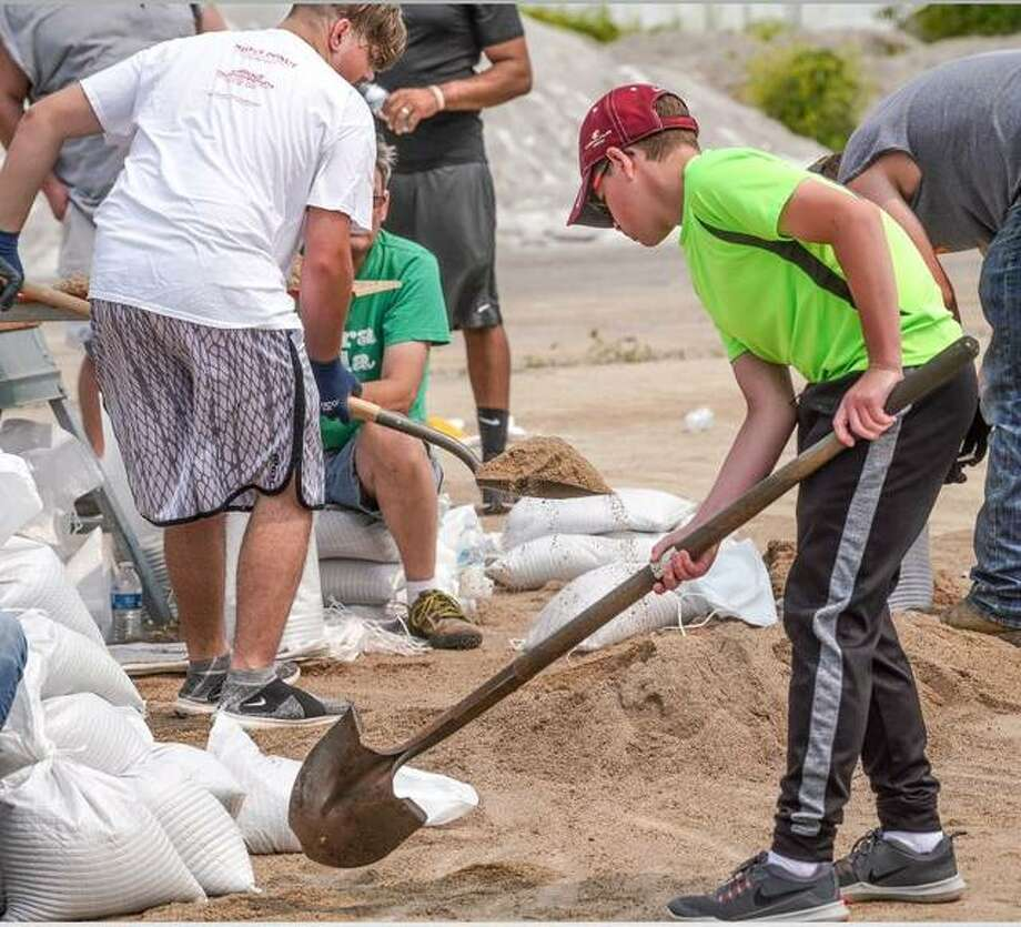 Volunteers sandbag Friday afternoon in Alton. Photo: Nathan Woodside | The Telegraph