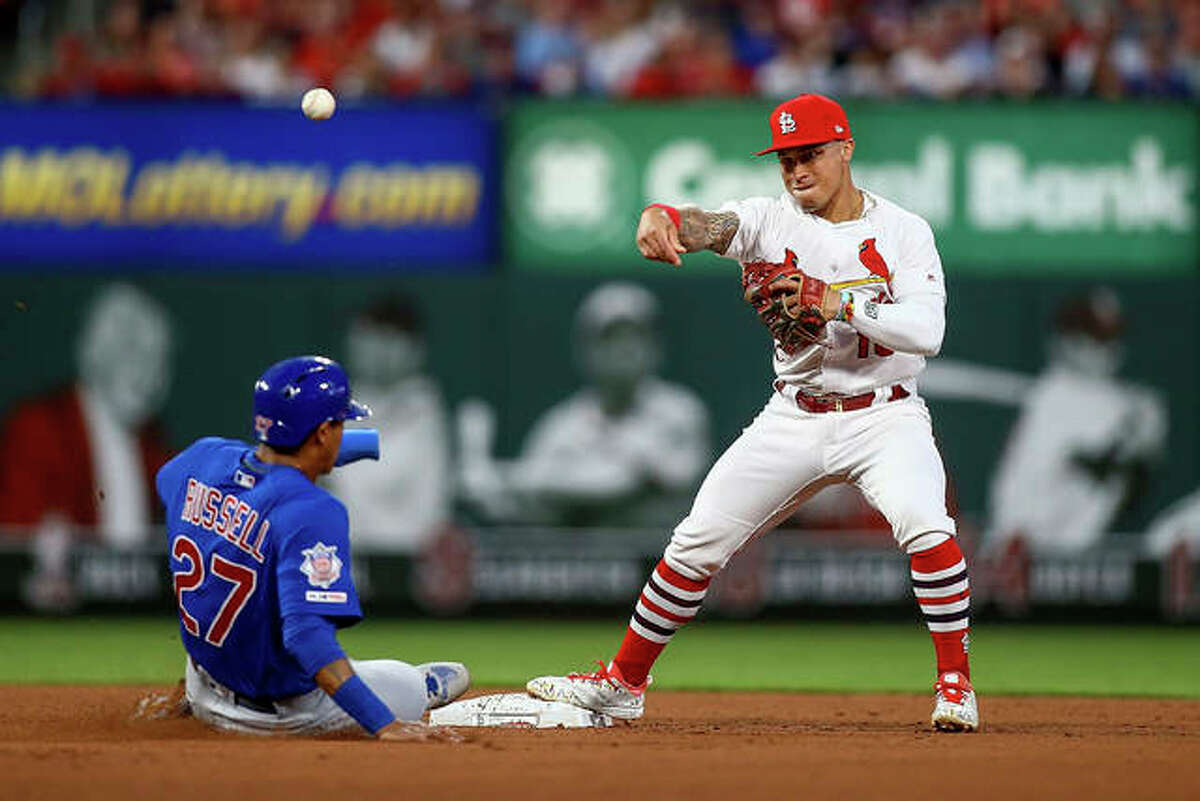 Cardinals second baseman Kolten Wong (16) turns a double play over the Cubs' Addison Russell in the fourth inning of Friday night's game in St. Louis. Albert Almora was out at first.