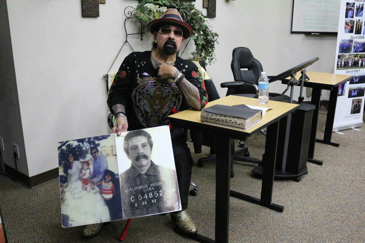 Pastor Sonny Lara sits in an office in San Jose and holds a photo of his family and his mug shot while incarcerated in San Quentin Prison. Lara is the founder and executive director of the Firehouse Community Development Corp. in San Jose.