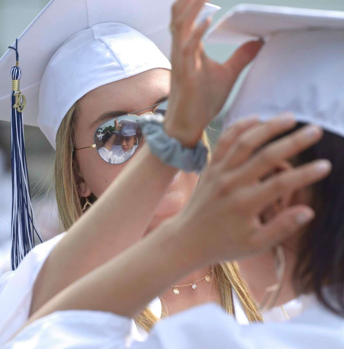 Vanesa Katherine Roma, of Danbury, adjusts the cap of Jessica Dennison, of Danbury, before the Immaculate High School 2019 Commencement. Saturday, June 1, 2019, at the Western Connecticut State University O'Neill Center, Danbury, Conn.