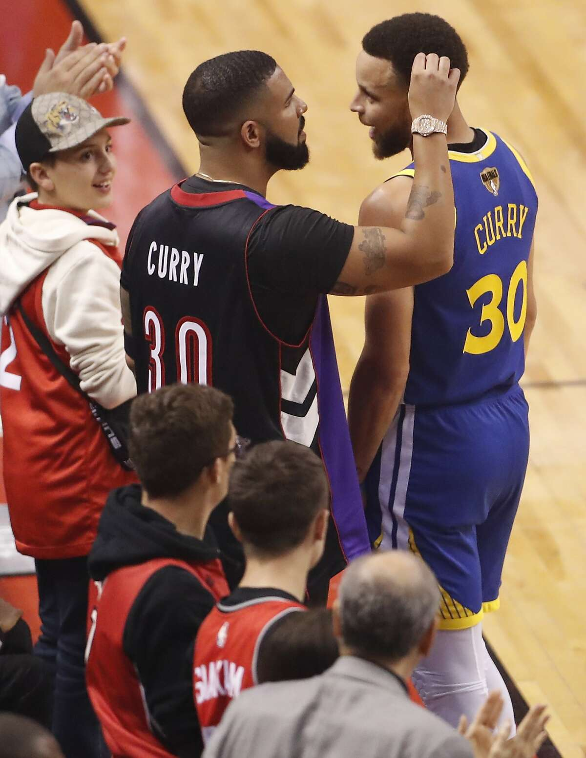 Drake and Golden State Warriors' Stephen Curry exchange pleasantries during Toronto Raptors' 118-109 win in NBA Finals' Game 1 at ScotiaBank Arena in Toronto, Ontario, Canada, on Thursday, May 30, 2019.