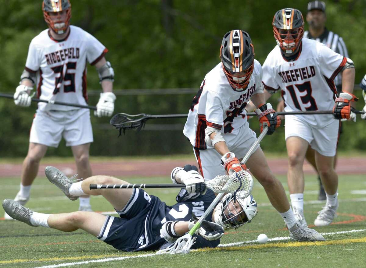 Staples Henry Beck (20) looses the ball as he hits the turf while being defended by Ridgefield's Kai Prohaszra (24) in the CIAC Class LL quarterfinal boys lacrosse game between No. 8 Staples and No. 1 Ridgefield high schools. Saturday, June 1, 2019, at Ridgefield High School, Ridgefield, Conn. Ridgefield's Connor Riebling (13) and Jack Dowd (25) are behind the play.