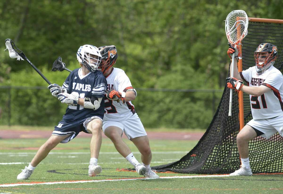 Staples Charlie Howard (21) puts pressure on Ridgefield goalie Daniel Parson (31) while being defended by Connor Riebling (13) in the CIAC Class LL quarterfinal boys lacrosse game between No. 8 Staples and No. 1 Ridgefield high schools. Saturday, June 1, 2019, at Ridgefield High School, Ridgefield, Conn.