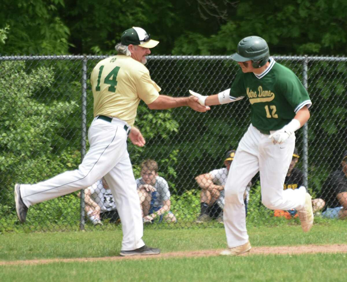 Notre Dame-West Haven's Colby Cusano high fives coach Don Martone after a home run in the Class L quarterfinals against Hand on Saturday.