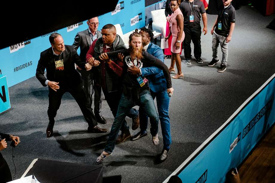 An animal rights protestor, center, is hustled off the stage by security during Senator Kamala Harris' (D-CA) speech during the MoveOn Big Ideas Forum conference held at the Warfield Theater in San Francisco, Calif., on Saturday, June 1, 2019. Photo: Michael Short / Special To The Chronicle