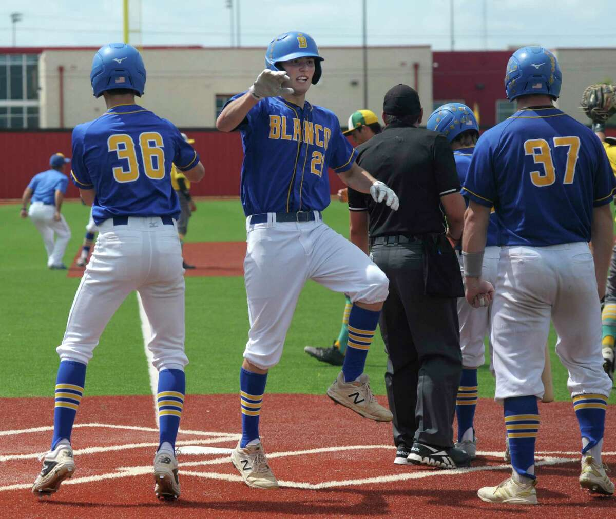 Blanco's Justin Wardlow (21) celebrates with teammates after scoring on a 7th-inning three-RBI triple by teammate Baylor Smith during Game 2 of the 3A regional final playoff series against Bishop in Jourdanton on Saturday, June 1, 2019. Blanco won and advances to the state tournament.