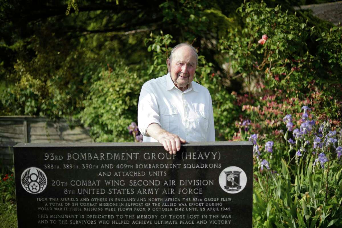 In this photo taken on Thursday, May 23, 2019, British D-Day veteran David Woodrow, 95, who landed at Gold beach and served in 652 squadron of the British Royal Air Force poses for photographs next to the memorial for the American 93 Bombardment Group (Heavy) on his family's farm, which during World War II served as part of Hardwick Airfield near the village of Topcroft, in Suffolk, eastern England. From 1942 to 1945 more than 2 million American military personnel were stationed in the U.K., and across the country people still commemorate their sacrifice. Britain is dotted with memorials, many built and still tended by local people who honor those who died and remember the thousands of others they drank and danced and fought with. (AP Photo/Matt Dunham)