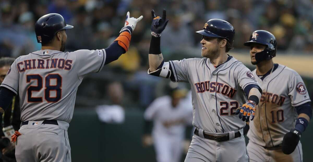 Houston Astros' Josh Reddick, right, celebrates with Robinson Chirinos (28) after hitting a two-run home run off Oakland Athletics' Brett Anderson during the fourth inning of a baseball game Saturday, June 1, 2019, in Oakland, Calif. (AP Photo/Ben Margot)