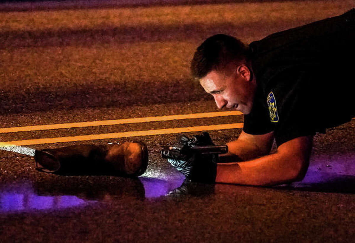 An Alton police officer closely examines the boot left by a pedestrian struck by a vehicle on Broadway Saturday night.