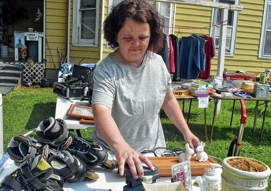 Bethanny McGee of Jacksonville arranges items on a table for a yard sale Saturday as a part of the Citywide Garage Sale. More than 80 households took part in the first-ever event. Photo: Samantha McDaniel-Ogletree | Journal-Courier