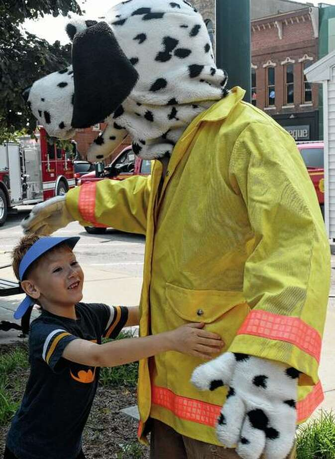 Kristafer Higgins, 6, the son of Sam Higgins and Nichole Busch of Jacksonville, greets Sparky the fire dog Saturday during the Elks Lodge Kid's Safety Day. The event in downtown Jacksonville brought together health, medical and law enforcement professionals to give children and parents information about staying safe during the summer. Photo: Samantha McDaniel-Ogletree | Journal-Courier