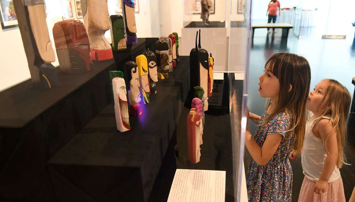 Jade Mechell, 6, left, and her sister Arial, 4, who were with their dad Chad, of Spring, check out the My Hero! Contemporary Art & Superhero Action exhibit.