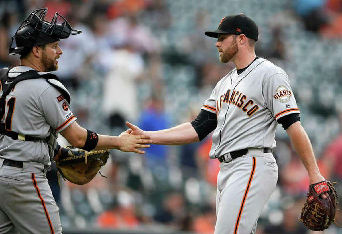 Giants relief pitcher Sam Coonrod (right), a 26-year-old right-hander from Carrollton, shakes hands with catcher Stephen Vogt after closing out a win over the Orioles with a perfect ninth Saturday in Baltimore.
