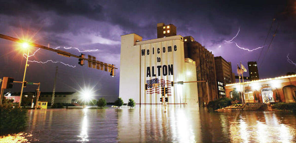 Lightning shoots across the sky late Saturday night as a storm blows through a flooded downtown Alton. The forecast for the crest of the Mississippi River is largely unchanged but has been moved to late Wednesday or early Thursday. However, rain and storms are in the forecast Tuesday through Sunday. The levee at West Alton has been topped and the town is under water.