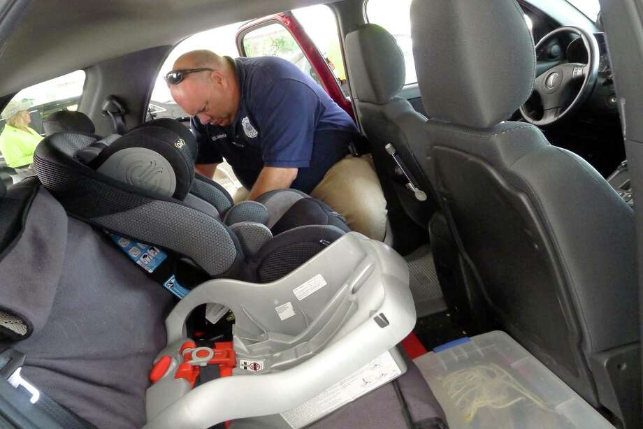 Coeymans Police Sgt. Dan Contento installs a car seat during the Albany County 15th annual child safety seat check at Colonie Center in Colonie N.Y. Friday June 8, 2012. (Michael P. Farrell/Times Union) Photo: Michael P. Farrell / 00017971A