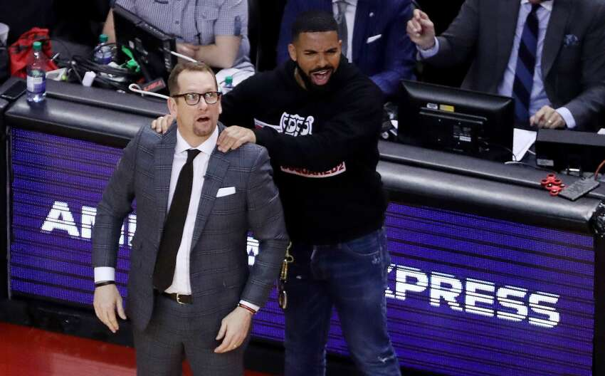TORONTO, ON- MAY 21 - Drake massages Toronto Raptors head coach Nick Nurse's shoulder as the Toronto Raptors beat the Milwaukee Bucks in game four 120-102 to even up the Eastern Conference NBA Final at two games each at Scotiabank Arena in Toronto. May 21, 2019.