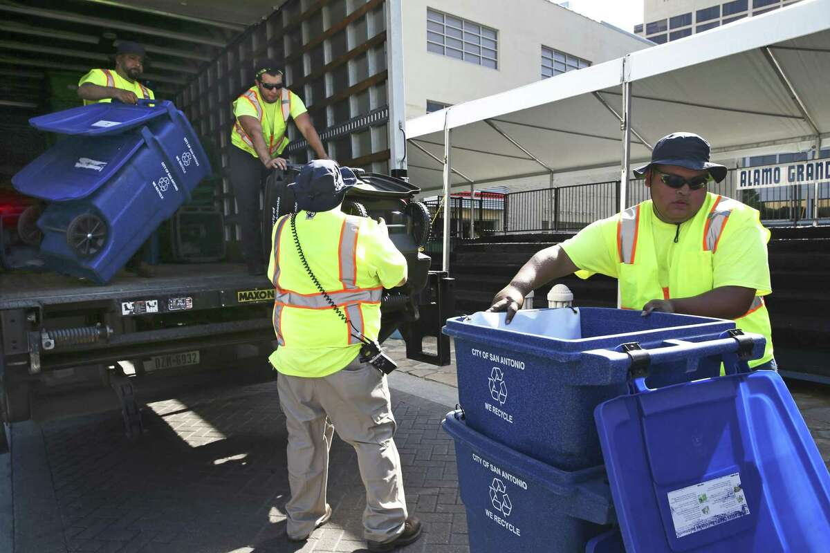 San Antonio solid waste workers place recycling containers and waste bins in Alamo Plaza as they make their way along the Fiesta parade route on April 21, 2016.