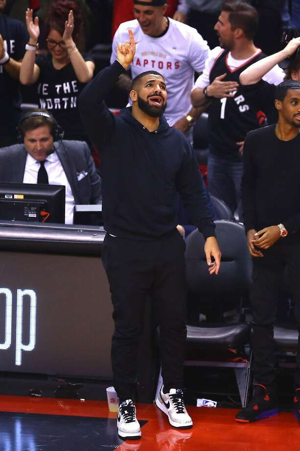 Drake reacts in the first half during Game Two of the 2019 NBA Finals between the Golden State Warriors and the Toronto Raptors at Scotiabank Arena on June 02, 2019 in Toronto, Canada. The front of his jersey is plain black, but the back has a message that's likely for injured Warriors star Kevin Durant. Photo: Vaughn Ridley, Getty Images