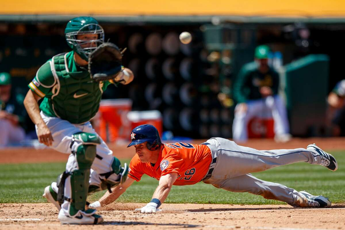 OAKLAND, CA - JUNE 02: Myles Straw #26 of the Houston Astros dives into home plate to score a run ahead of a tag from Nick Hundley #3 of the Oakland Athletics during the fifth inning at the Oakland Coliseum on June 2, 2019 in Oakland, California. (Photo by Jason O. Watson/Getty Images)