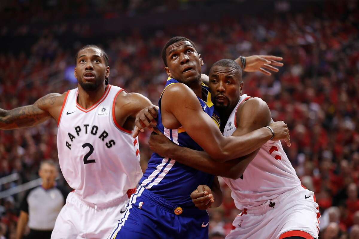 Golden State Warriors' Kevon Looney and Toronto Raptors' Serge Ibaka fight for position in the first quarter during game 2 of the NBA Finals between the Golden State Warriors and the Toronto Raptors at Scotiabank Arena on Sunday, June 2, 2019 in Toronto, Ontario, Canada.