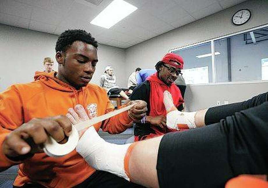 Kameron Graham (left) and Nate Moore practice taping ankles on fellow student Alex Vogt during a prevention and treatment of athletic injuries class in the Millikin University Exercise Science and Sports Pavilion in Decatur. Photo: Jim Bowling | Herald & Review (AP)