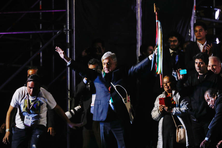 Andres Manuel Lopez Obrador, Mexico's president (center) holds up a ceremonial wooden staff during the 58th presidential inauguration event in Mexico City on Dec. 1, 2018. Photo: Bloomberg Photo By Alejandro Cegarra. / © 2018 Bloomberg Finance LP