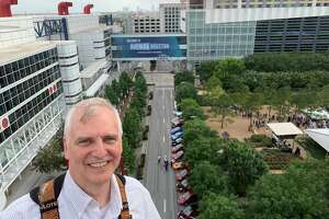 Houston Electric Auto Association President Dave Hanson poses for a photo looking on the the George R. Brown Convention Center, where across the street various electric vehicles are on display during the American Wind Energy Association conference in late May.