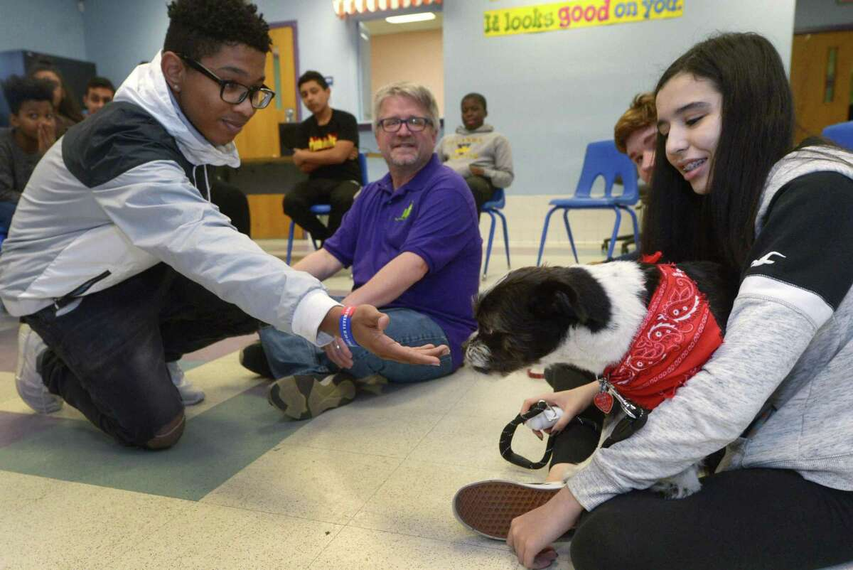 Children at the Norwalk Housing Authority Learning Center at 20 West Avenue including Carlos Aguero, 13, Zeus, a dog with Stepping Stones Museum for Children Mutt-i-grees program, while program coordinator Dod March and Youth Enrichment at Stepping Stones ambassador Jennifer Costa look on, Wednesday, March 28, 2018, at the Learning Center in Norwalk, Conn.