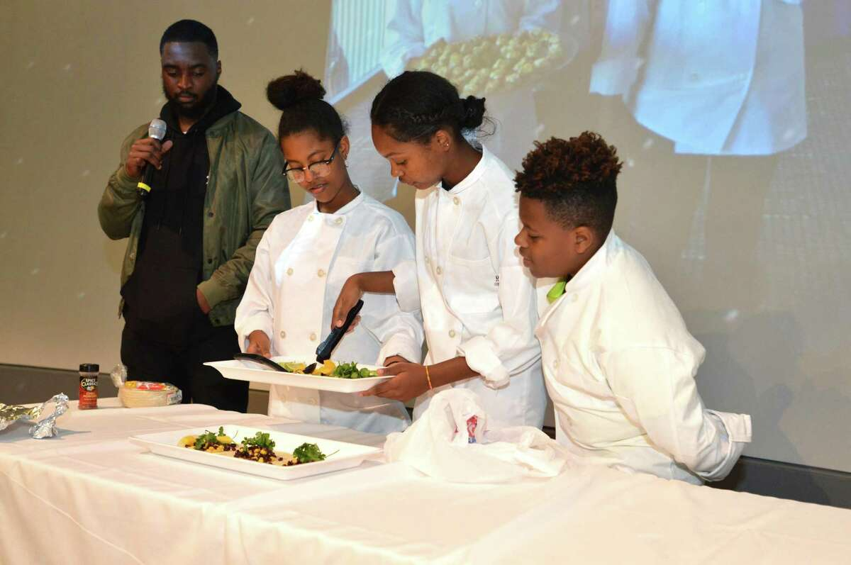 The Teen Chef program, Kimberly Castillo, Maika Silvestre and Leyin Grant make mango black bean tacos on stage with help from Educational Coordinator David Pierre-Charles on Thursday October 26, 2017 in Norwalk Conn.
