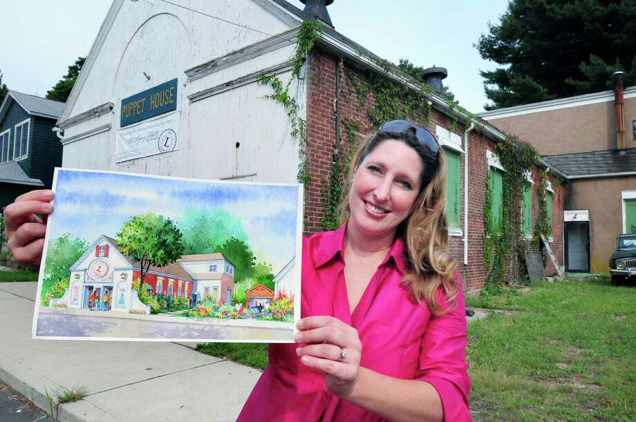 Keely Baisden Knudsen, artistic director of the Legacy Theatre, holds an artist's rendering of plans for the former Puppet House (background) in the Stony Creek section of Branford. Photo: Arnold Gold / Hearst Connecticut Media File