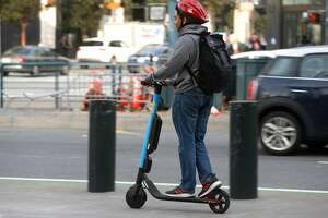 A commuter rides a Skip e-scooter on the sidewalk in front of Oracle Park on King Street in San Francisco, Calif. on Tuesday, March 19, 2019.