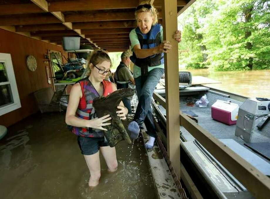 Emily Kientzel empties the water out of her grandmother Joan FitzGerald's boot that filled with floodwater from the Mississippi River, as they check on the home of a friend outside of Portage des Sioux, Mo., Sunday. The pair are standing on the second story balcony of the home that has more than a foot of water in it. Photo: David Carson, Via AP