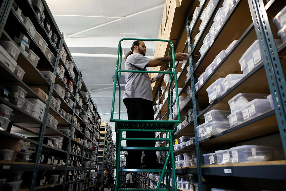 Joseph Maldonado pulls items from a shelf as he fills an order at the headquarters of online luxury resale and consignment company The RealReal in San Francisco, CA, Wednesday June 18, 2014.