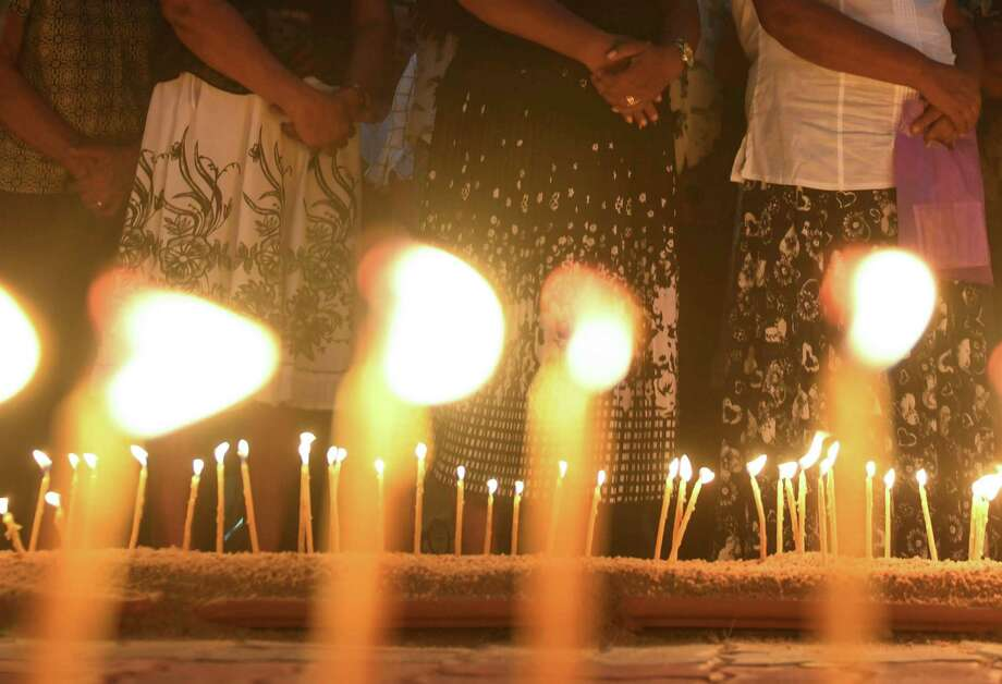 Sri Lankan Christian devotees stand in front of candles lighted outside St Sebastian's Church in Negombo on May 21, 2019, a month after Easter Sunday bombings that killed 258 people. (Photo by LAKRUWAN WANNIARACHCHI / AFP)LAKRUWAN WANNIARACHCHI/AFP/Getty Images Photo: LAKRUWAN WANNIARACHCHI, Contributor / AFP/Getty Images / AFP or licensors