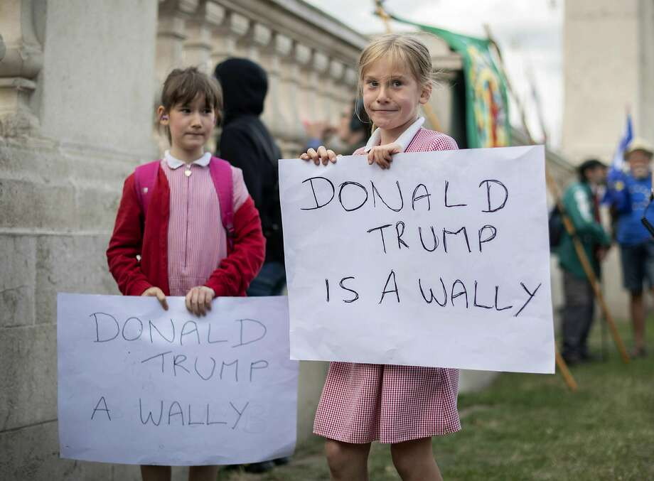 Two young protestors hold banners outside Buckingham Palace, during the first day of a state visit by US President Donald Trump, in London, Monday June 3, 2019. (David Mirzoeff/PA via AP) Photo: David Mirzoeff, Associated Press