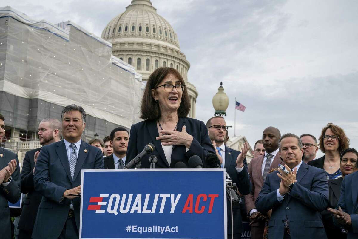 """Transgender rights activist Mara Keisling joins advocates for LGBTQ rights as they rally before a vote in the House on the """"Equality Act of 2019,"""" sweeping anti-discrimination legislation that would extend civil rights protections to LGBT people by prohibiting discrimination based on sexual orientation or gender identity, at the Capitol in Washington, Friday, May 17, 2019. She is flanked by Rep. Mark Takano, D-Calif., left, and Rep. David Cicilline, D-R.I., right, the chief sponsor of the bill to protect LGBTQ rights. (AP Photo/J. Scott Applewhite)"""
