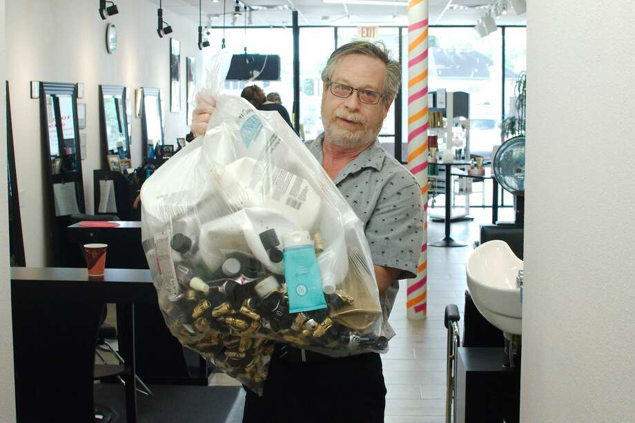 Hair Color Experts owner Perry Lazer holds a bag of beauty product containers ready to be sent to Dragon Master Foundation Friday, May 31. Photo: Kirk Sides/Staff Photographer