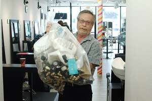 Hair Color Experts owner Perry Lazer holds a bag of beauty product containers ready to be sent to Dragon Master Foundation Friday, May 31.