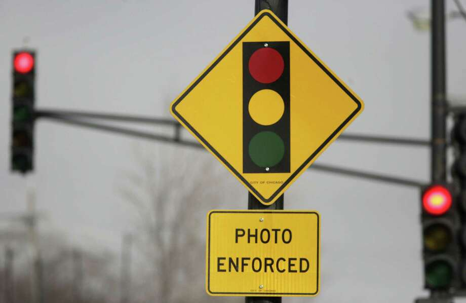 FILE - In this Tuesday, Feb. 10, 2015 file photo, a sign warns motorists of the presence of a red light camera in Chicago. Texas Gov. Greg Abbott signed a law Saturday, June 1, 2019 that bans red-light traffic cameras in Texas. (AP Photo/M. Spencer Green, File) Photo: M. Spencer Green, STF / Associated Press / Copyright 2019 The Associated Press. All rights reserved.