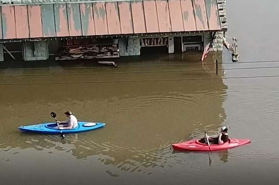 Kayakers drift down East Main Street in Grafton Sunday, in front of Knotty By Nature. Photo: Nathan Woodside | The Telegraph