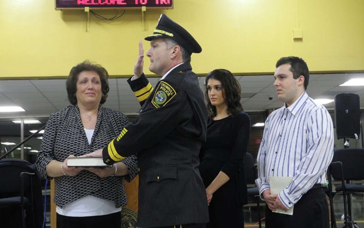 Police Chief Michael Lombardo, with wife Cathy and children, Dana and Michael, takes the oath of office Wednesday night.