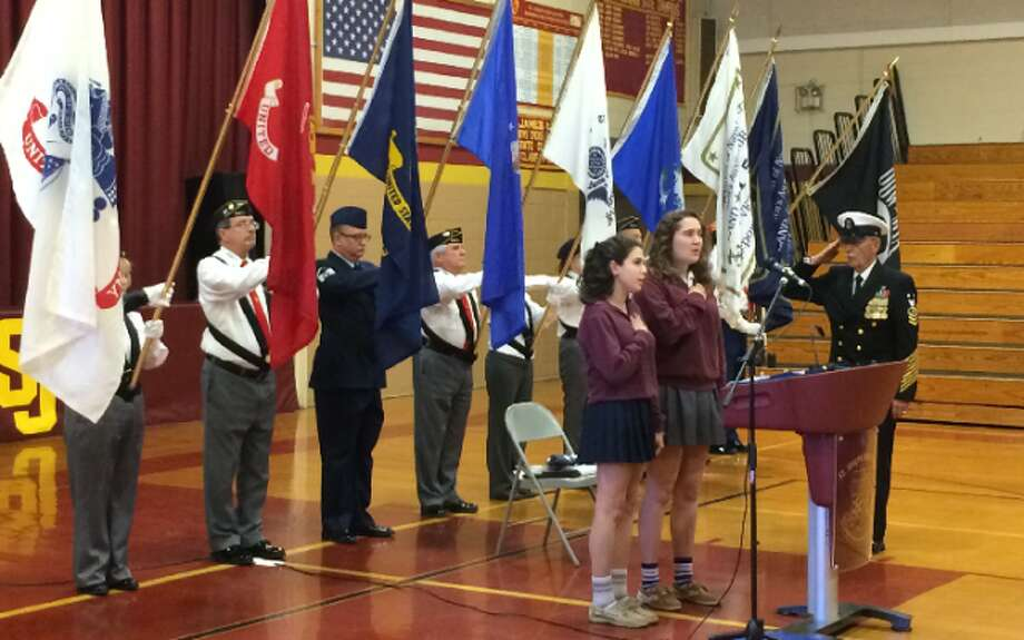Master Chief Richard Iannucci salutes during the playing of the National Anthem before Friday's Veterans Day assembly at St. Joseph High School. — Donald Eng