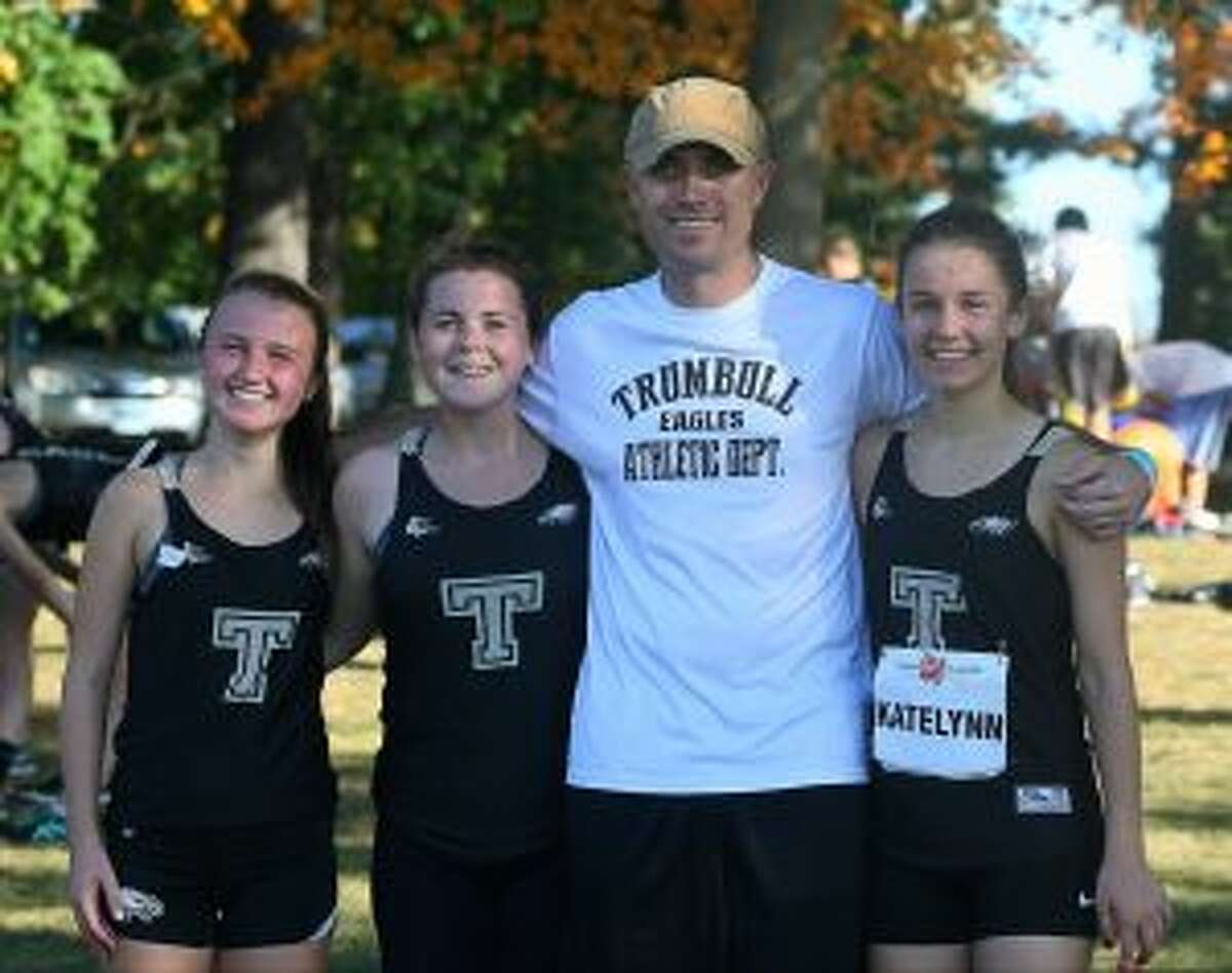 Trumbull High girls cross country coach Jim McCaffrey gets together with varsity runners Kaley Fasoli, Maggie LoSchiavo and Kate Romanchick.