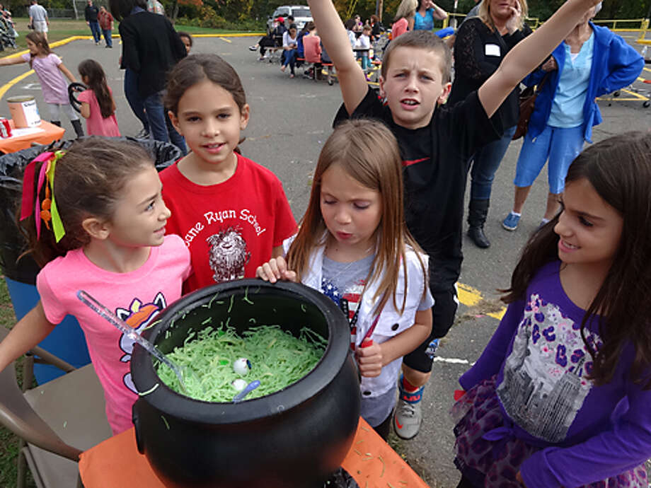 Madeleine Valiante, Elise Daly, an unidentified stew fan, and Kayla Ward (with a photobomb by George Kane) stare into the eyeball stew, one of the many games at the Jane Ryan Pumpkin Fair from a previous year.