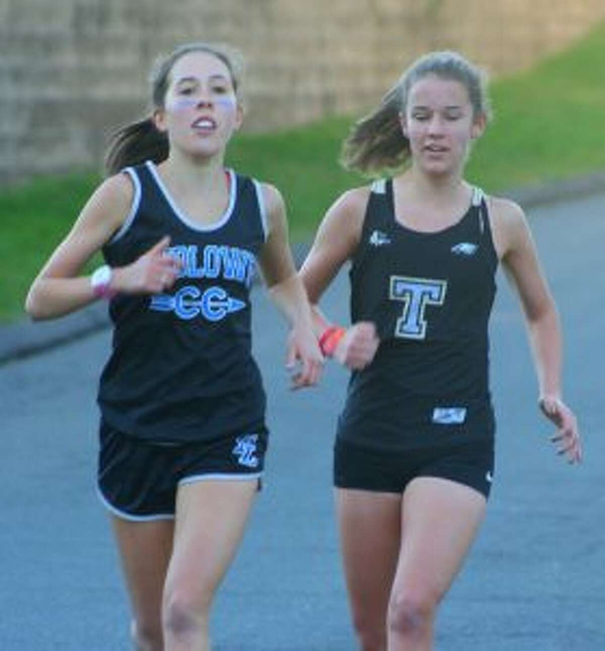 Fairfield Ludlowe's Sarah Leatherwood and Trumbull High's Kate Romanchick run side by side in Monday's meet.