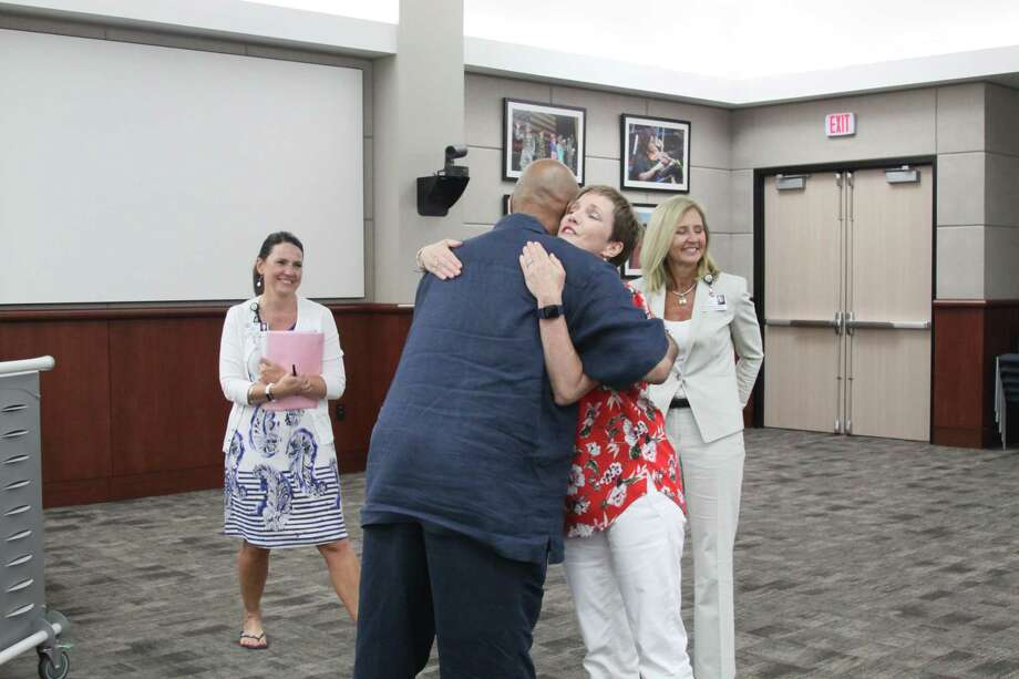 Cypress-Fairbanks ISD board president John Ogletree hugs Julie Hinaman after she is selected as the new trustee to fill the vacancy on position 2. Photo: Mayra Cruz