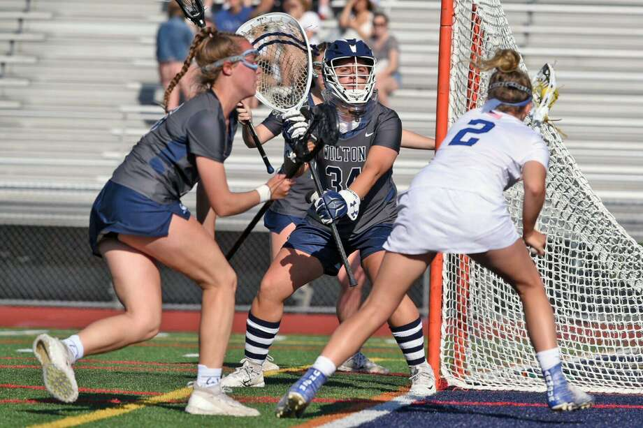 Wilton goalie Bridgette Wall and Meghan Lane (16) defend against Darien's Ashley Humphrey (2) during the CIAC Class L girls lacrosse semifinals at Brien McMahon High School on Monday, June 3, 2019. Photo: David Stewart / Hearst Connecticut Media / Connecticut Post
