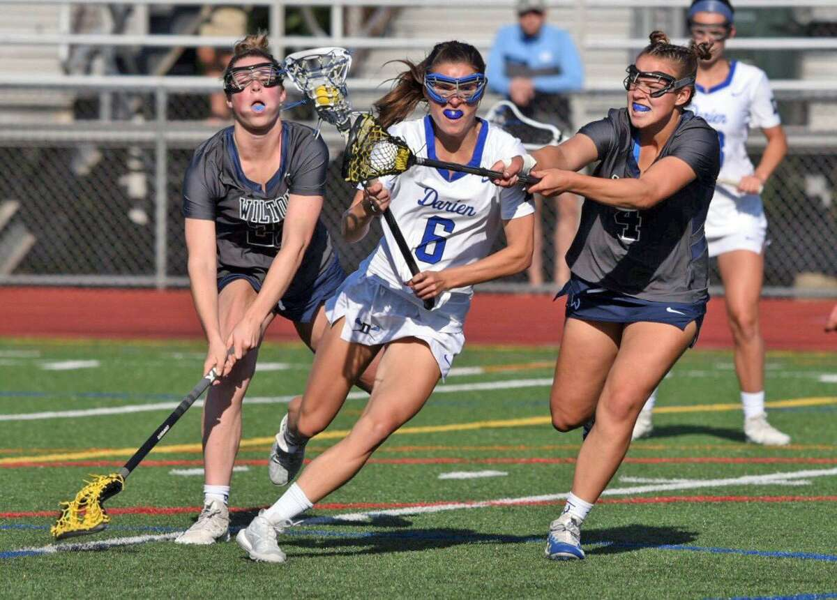 Darien's Katie Elders (6) takes on Wilton's Delaney Liston (21) and Delia Frelich (4) during the CIAC Class L girls lacrosse semifinals at Brien McMahon High School in Norwalk on Monday.